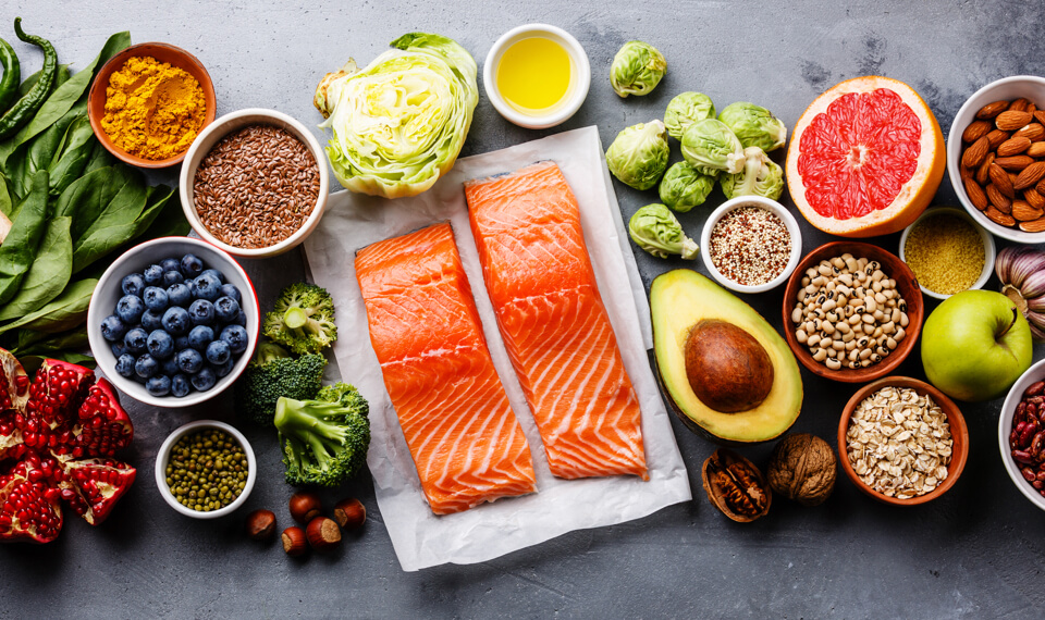 Display of foods that fight cancer including salmon, avocado, oats, grapefruit, broccoli, and more