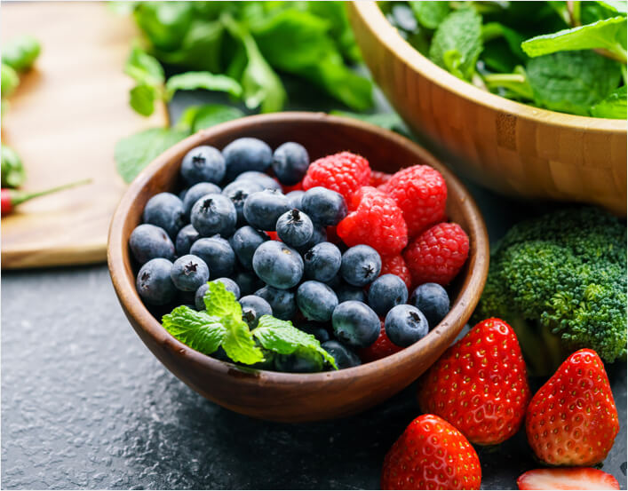 Bowl of berries alongside bowl of green vegetables