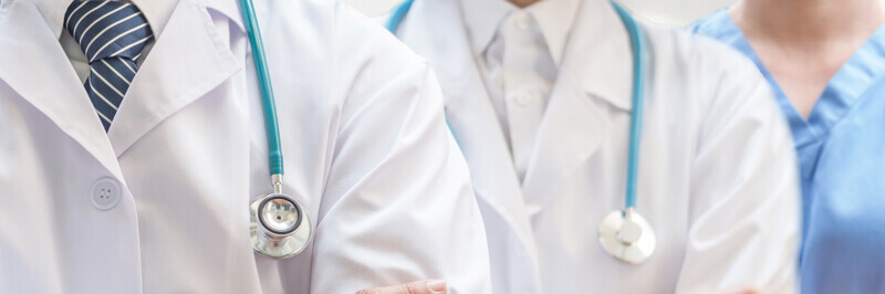 Banner with three doctors in a line wearing stethoscopes